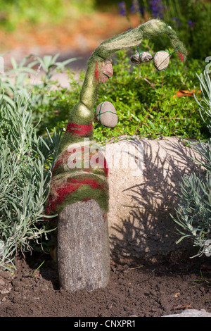 'felt stone troll' serving as garden decoration: a natural stone equipped with caps of felted wool is standing in - Stock Photo
