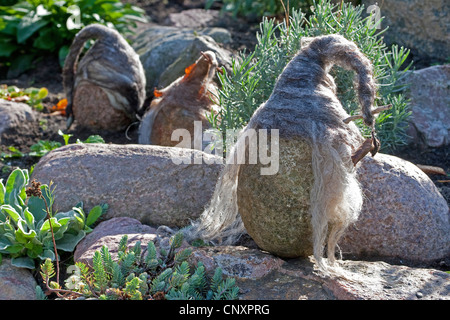 'felt stone trolls' serving as garden decoration: three natural stones equipped with caps of felted wool are standing - Stock Photo