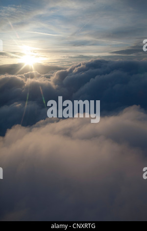 sunburst above the clouds from an aircraft - Stock Photo