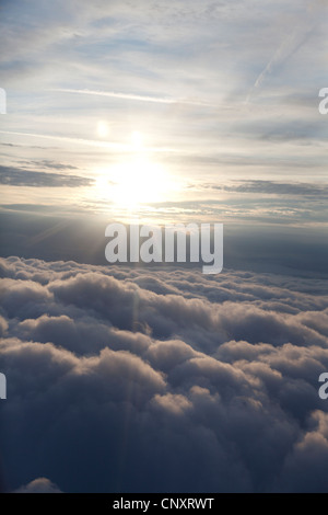 sun above sky from an aircraft with blanket of cloud - Stock Photo
