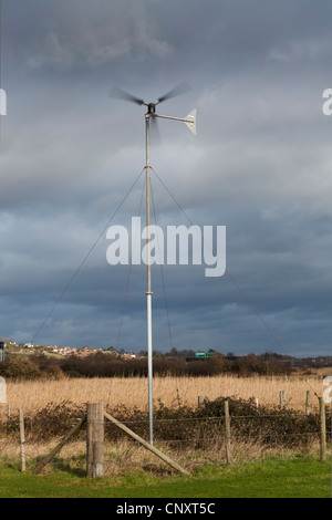 small rural wind power generator against stormy overcast cloudy sky - Stock Photo
