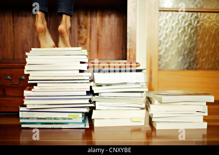Girl stands tiptoe on pile of books - Stock Photo