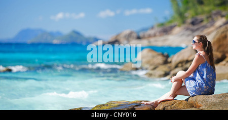 woman sitting on top of granite rock at beach and enjoying a good view, Seychelles, La Digue, Anse Source d'Argent - Stock Photo