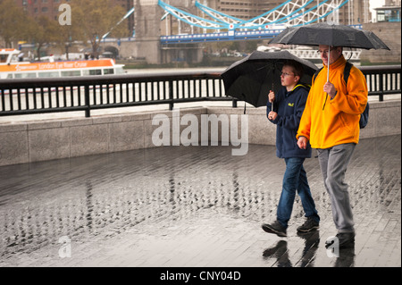More London Southbank father & son with black umbrellas walking past City Hall heavy rain downpour Tower Bridge - Stock Photo