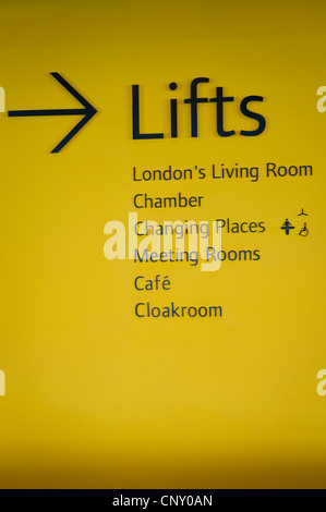 London City Hall Southbank yellow wall black lettering sign signs to amenities - Stock Photo