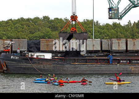 canoeists in front of a cargo ship in the coal harbour Auguste Victoria at the Wesel-Datteln Canal, Germany, North - Stock Photo
