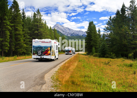 three travel vans on a road through the National Park, Canada, Alberta, Banff National Park - Stock Photo