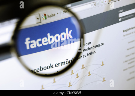 the Facebook logo under a magnifying glass symbolising the platform's legally doubtful handling of private data - Stock Photo