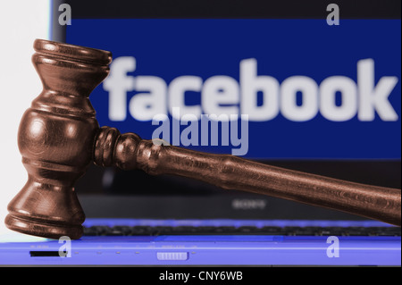 the Facebook logo under a magnifying glass symbolising the legally doubtful aspects of the platform - Stock Photo
