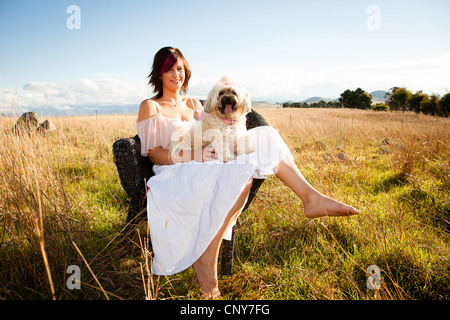 Woman in a field with a poodle on her lap - Stock Photo