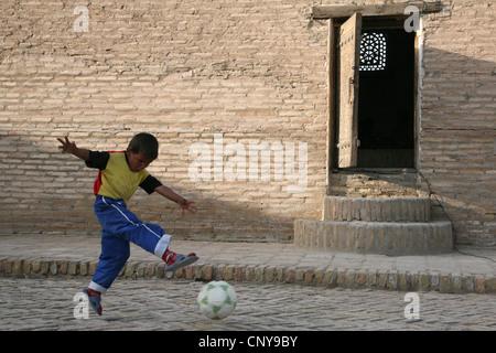 Uzbek boy play football in Itchan Kala, a medieval walled inner town, in Khiva, Uzbekistan. - Stock Photo