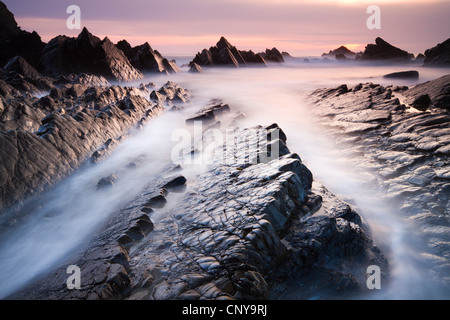 Dramatic coastal scenery at sunset, Hartland Quay, Devon, England. Spring (April) 2010. - Stock Photo