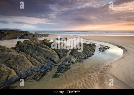 Sunset on the rocky and sandy beach at Combesgate, Woolacombe, Devon, England. Summer (June) 2010. - Stock Photo