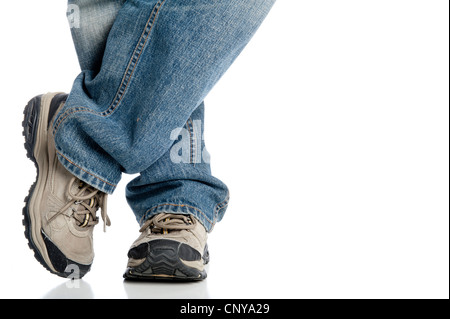 Close-up of man's feet and athletic shoes while standing casually with one foot crossed in front of the other, isolated - Stock Photo