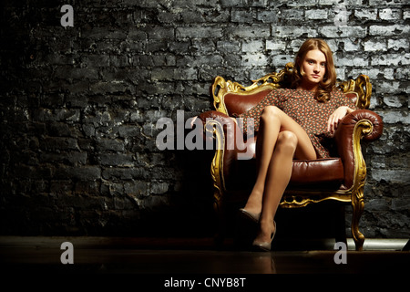 Image of elegant girl sitting in retro style armchair and looking at camera - Stock Photo