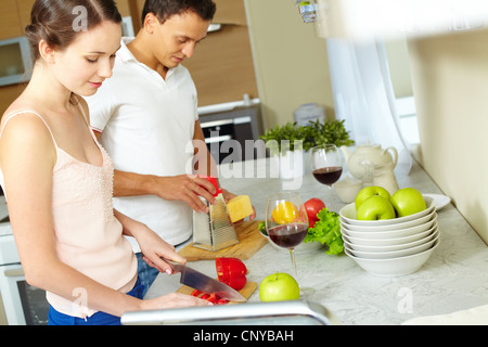 Tilt up of a sweet couple cooking together at home, girl cutting paprika while her man grating cheese - Stock Photo