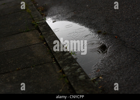 A puddle of water with beautiful rings in it - Stock Photo