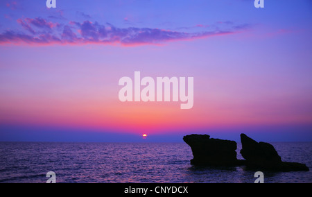 Beautiful purple sunset on the beach, seascape with calm ocean and rocks in the blue water - Stock Photo
