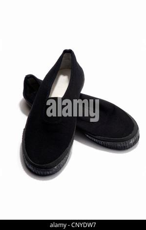 A pair of black plimsolls - Stock Photo