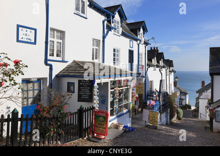 Local shop on steep narrow cobbled street in quaint picturesque village with view to the sea in Clovelly North Devon - Stock Photo