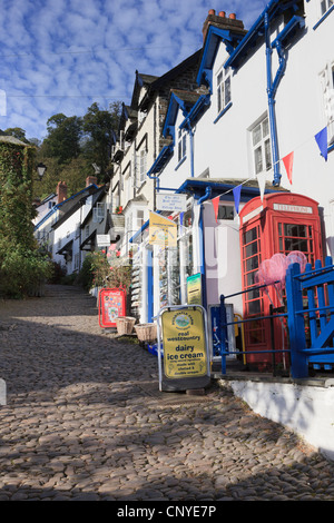 View up steep narrow cobbled street in quaint village with shop and red telephone box in Clovelly Devon England - Stock Photo