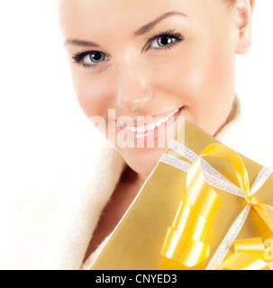 Close up on smiling face with gift, beautiful female with present, pretty young girl holding golden box, portrait - Stock Photo