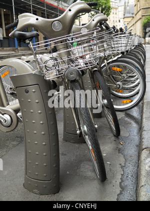 Bicycles for rent at one of the many bike stations in Paris, part of the 'Velib' scheme of cycle hire extending - Stock Photo
