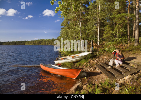 mother and daughter sitting at the shore of Lake Algunnen, Sweden, Sm�land, Alsterbro - Stock Photo