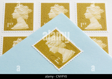UK, Britain. Royal Mail first class postage stamps and an envelope with a stamp stuck on - Stock Photo