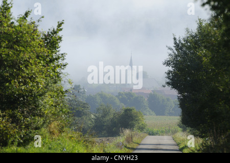 narrow road leading to a village veiled by morning mist, Germany, Bavaria, Upper Palatinate - Stock Photo