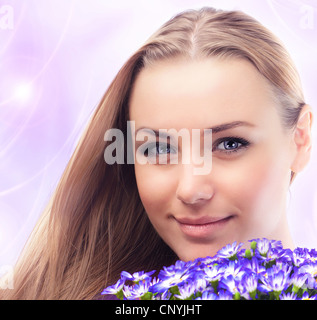 Girl face with bouquet of spring plant, bunch of purple cornflowers, lovely woman with gift over pink abstract background - Stock Photo