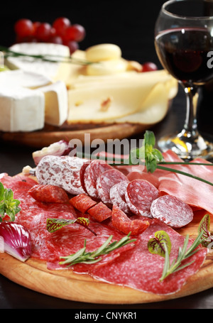 Salami and cheese platter with vegetable and herbs - Stock Photo