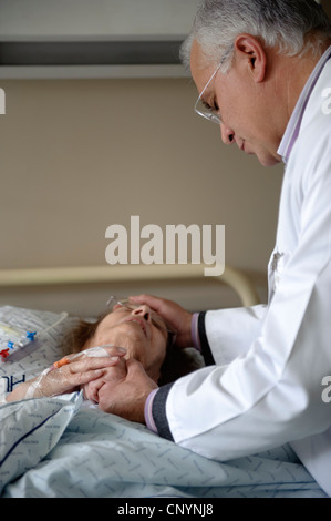 Doctor comforting patient and holding her hand in hospital ward - Stock Photo
