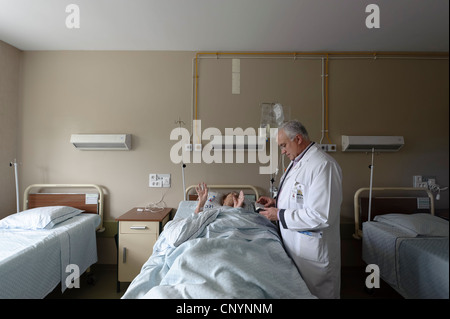 Doctor next to patient's bed in hospital ward - Stock Photo