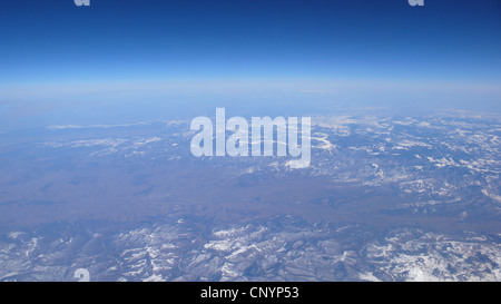 view over a vast mountain landscape from a plane window - Stock Photo