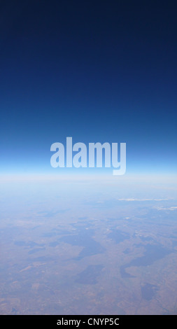 view out of plane window on a cloudless sky over a vast landscape - Stock Photo