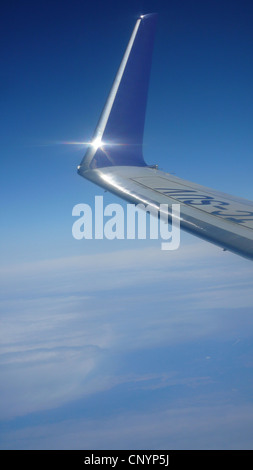 view out of the window of a plane flying high above the clouds on an empennage at a wing - Stock Photo