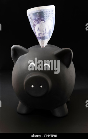 Black Piggy Bank with a £20 note sticking out of the top. On black background - Stock Photo