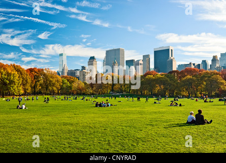 People relaxing in Central Park, New York City, in Autumn, looking towards the Central Park South skyline from Sheep - Stock Photo