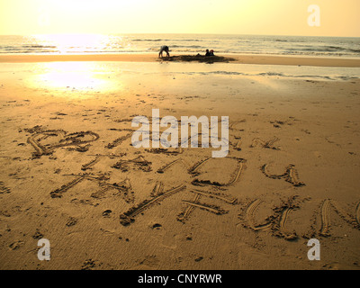 a father is building a sand castle with his boys whose names he has written into the sand, Germany, Mecklenburg - Stock Photo
