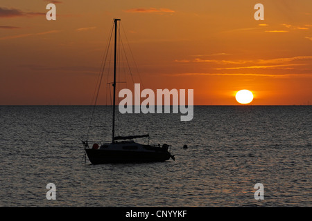 sailing boat on the sea in front of sunrise, Germany, Schleswig-Holstein, Sylt - Stock Photo