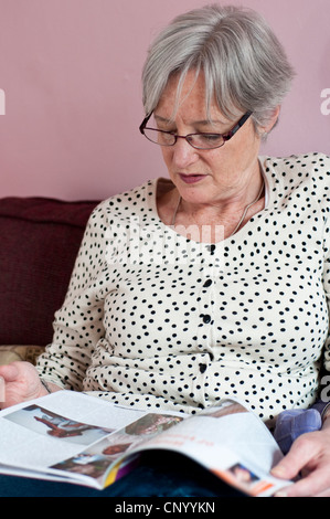Portrait of middle aged woman reading a magazine - Stock Photo