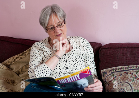 Portrait of middle aged woman reading the magazine called Identity - Stock Photo
