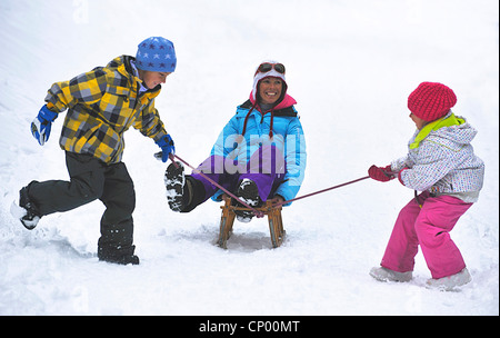 mother sitting on a sled having fun being pulled by her two sons, France - Stock Photo