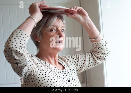 Middle aged woman with a plate on top of her head looking puzzled - Stock Photo