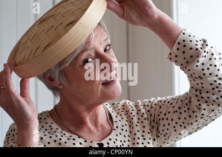 Middle aged woman playing with bamboo lid in kitchen - Stock Photo