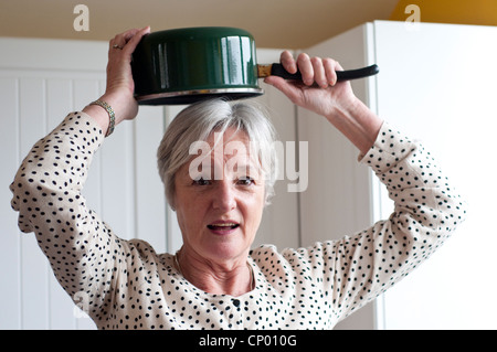 Middle aged woman holding saucepan above her head looking puzzled - Stock Photo