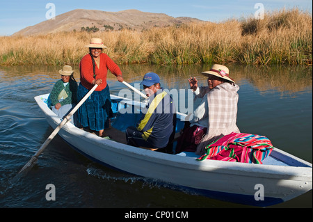 four Quechua or Uros Indians in a rowing boat on Lake Titicaca at one of 42  floating islands called 'Uros Islands', - Stock Photo