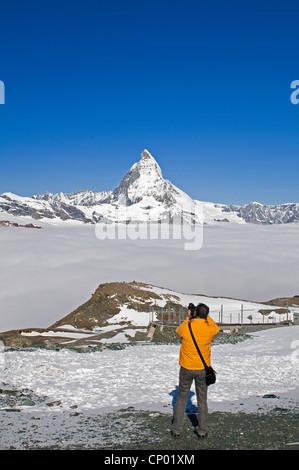 tourist on Gornergrat taking a photo of Matterhorn, Switzerland - Stock Photo