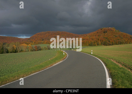 country road in a autumn landscape with ruins of Gleichenstein castle, Germany, Thueringen, Martinfeld - Stock Photo